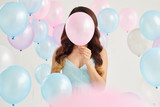 Young woman holding pink balloon in front of her face