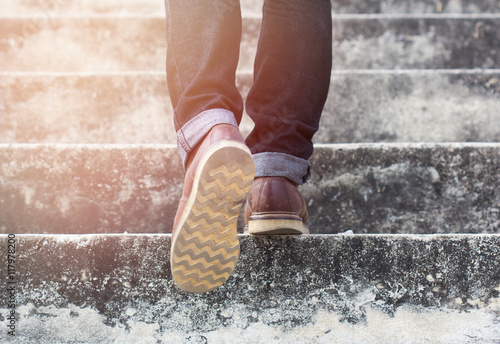 a man with blue geans and sneaker shoes in stair