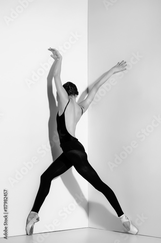 Naklejka Ballerina in black outfit posing on pointe shoes, studio background.