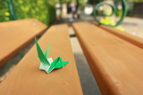 Paper crane resting on wooden bench