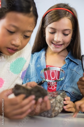 Kids looking at specimen stone through magnifying glass