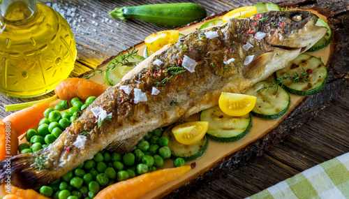 Fototapeta Grilled trout fillets with vegetables on wooden background