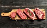 Fresh raw Prime Black Angus beef steaks on wooden board - 118025465