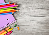 Education supplies on old wooden background. Colorful pencils