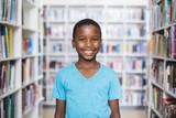 Happy schoolboy standing in library