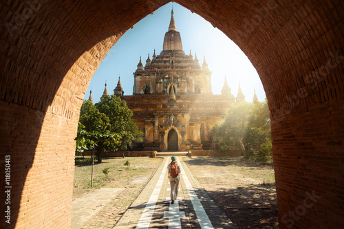 Poster Traveler walking along road to Htilominlo temple in Bagan. Burma