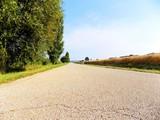 Asphalt road between fields