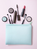 Aerial view of a make up bag with cosmetic products spilling out on to a pastel pink background