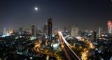Night cityscape of Bangkok, the capital of Thailand. Modern urban architecture, transport traffic and illuminated streets