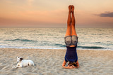 Fototapety Young woman doing yoga Headstand on the beach with his dog - inverted posture - Sirsasana