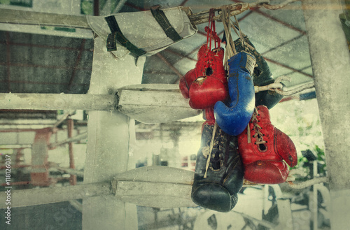 Póster Un par de viejos guantes de boxeo Muay Thai se cuelga en el ring de boxeo en un barrio pobre efecto camp