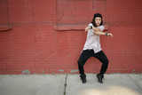Young Asian woman dancing hip hop in city