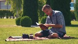 Young man relaxing reading a book outdoors on a rug in the garden as he enjoys the summer sun with coffee and a tablet in front of him.