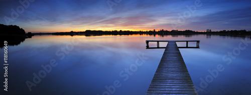 Drewniane molo w spokojne jezioro o zachodzie słońca