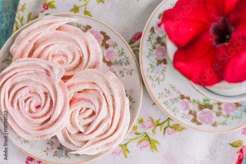 Poster Meringue cakes in the form of roses in a romantic dish with red