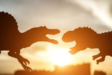 silhouette of spinosaurus and tyrannosaurus with buildings in far end in sunset time