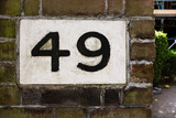 Hand-painted decorative house number tile on a brick wall – 49 (forty-nine)