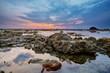 Colourful sunrise, orange coral and stones in  low tide ocean wa