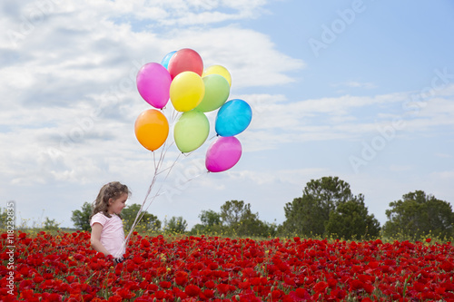 Poster Little girl on  field with wild flowers and many colorful balloons
