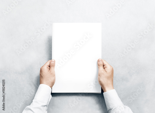 Hand holding white journal with blank cover mockup Poster