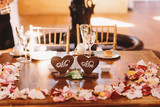 Wooden table covered with petals ant decorated with woodeh heart