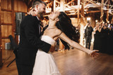 Fototapety Bride shakes her dark hair while dancing with a groom in wooden