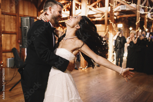 Bride shakes her dark hair while dancing with a groom in wooden