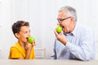Grandfather and grandson are eating apples at home. Healthy lifestyle.