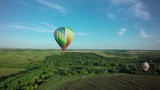 Balloons fly up in sky with passengers over green field