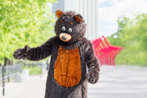 actor dressed as bear walks avenue of park on background of red stars Poster