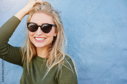 Pretty young woman in sunglasses smiling Poster