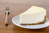 Fototapety Piece of plain New York Cheesecake on white plate on wooden table, close up view