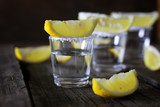 stack of tequila with salt and lemon on a wooden background