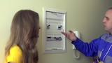Electrician man explain for housewife woman client how to use circuit breaker box