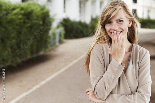 Shy girl giggling in park, portrait Poster
