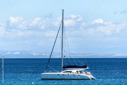 Sailboat yacht is moored in the sea bay.