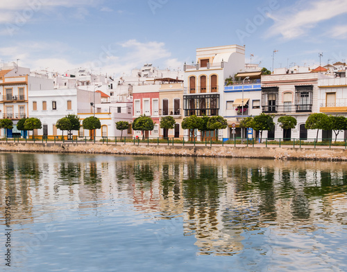 Zdjęcia na płótnie, fototapety, obrazy : Traditional white architecture of the region along the riverbank in Ayamonte, Huelva province, Andalucia, Spain.  The buildings and clouds are reflecting in the river.