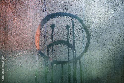 Sad upside down smiley hand drawn symbol on wet glass background. Poster