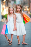 Adorable little girls on shopping. Portrait of kids with shopping bags in small italian town