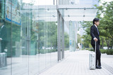 Businessman is standing in front of the building with a suitcase