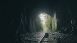 Woman walking to the light over the rails of an abandoned train in a dark tunnel