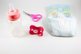 Baby bottle, nipple and scissors on a white background