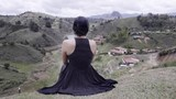 Hispanic woman seated on the edge of a panoramic site contemplating the  the mountains Guatape, Colombia. 4k