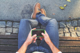 Man using cellphone on a bench in the park.