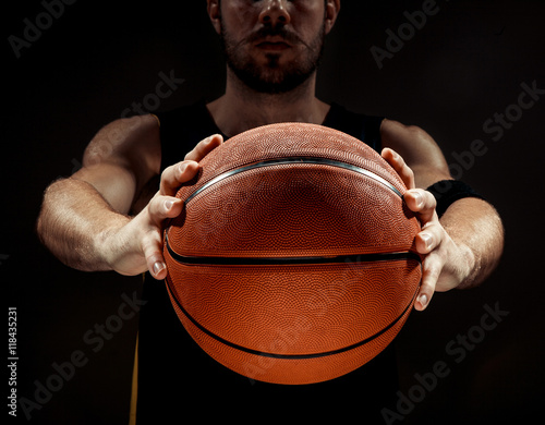 Plexiglas Silhouette view of a basketball player holding basket ball on black background
