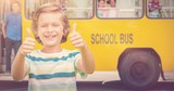 Composite image of boy showing thumbs up while smiling