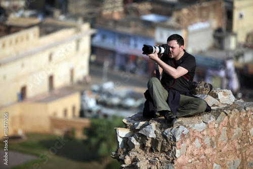 Poster photographer sitting on a rock high above the city blocks and removes Indian cit