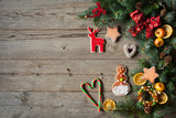 Christmas background with fir branches, ornaments, apples and biscuits