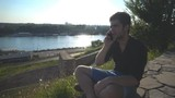 Handsome young man talking at smart phone in sunset in front of river