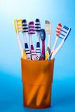 Zahnbürsten in orangenem Becher vor blauem Hintergrund.